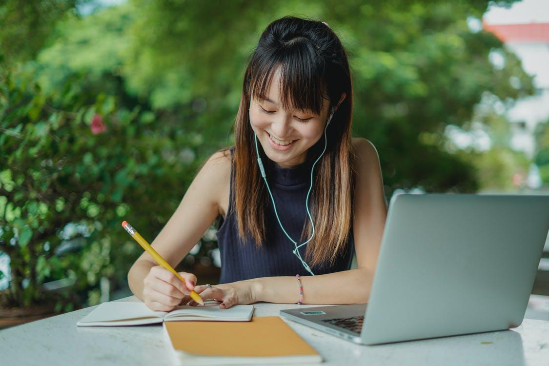 Positive young Asian female student with earphones writing in copybook while doing homework at table with laptop in street cafeteria